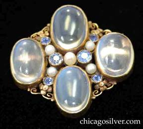 Brooch, by Edward Oakes, hand wrought in 14K green gold with four blue moonstones with six Montana sapphires and five seed pearls.  Fine, delicate and highly detailed foliate and scroll work between the gem stones.  Excellent work.