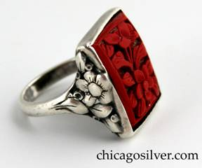 Ring, by Edward Oakes, silver, with bezel-set rectangular cinnabar stone deeply carved with floral motif inside frame.  Sides have similar flower and leaf design.  Owned by a Wakefield, Massachusetts neighbor of Oakes who had it custom made by Oakes.