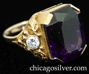 Ring, by Gilbert Oakes, handwrought in 14K gold with central faceted amethyst with deep color, flanked by bezel-set diamonds with fine, highly detailed gold work depicting leaves, scrolls and small beads.  Beautifully crafted.