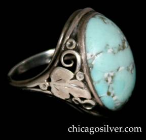Ring, by Gilbert Oakes, handwrought in sterling silver with central, oval, light blue turquoise cabochon.  The shank has applied silver foliate and leaf ornament with beads and scrolls.  Shank is worn.