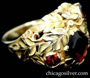 Ring, by Susan Oakes Peabody, hand wrought in 14K gold with three faceted garnets with deep red color and two small diamonds.  The stones are set among fine, highly detailed gold work depicting leaves, scrolls and small beads.  The diamonds are set inside gold flower blossoms.  Beautifully crafted, heavy.