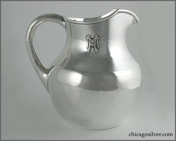 "Kalo pitcher, on flat bottom, with body flaring outward from foot to just above middle, then tapering inward with narrow neck and V-shaped spout.  Applied wire to rim.  Small looping hollow handle, applied HM mono on side.  Gently hammered surfaces.  From the Estate of Mary and Frank J. Mackey, Jr.  7-1/8"" W and 7-1/8"" H.  STERLING / HAND WROUGHT / AT / THE KALO SHOPS / CHICAGO / AND / NEW YORK / 9317 / 4 PTS"