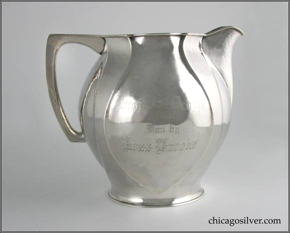 "Kalo pitcher, water, bulbous form with four paneled sides and alternating, recessed, inverted spade shapes with flat top hollow handle.  Side is engraved ""Presidents Trophy 1913 Won by Ross Brooks.""  Underside is engraved ""Presented By Albert J. Buckheit.""  Nicely hammered surfaces.  7-1/4"" H and 8-1/2"" W.  STERLING / HAND WROUGHT / AT / THE KALO SHOPS / CHICAGO / AND / NEW YORK / 10429"