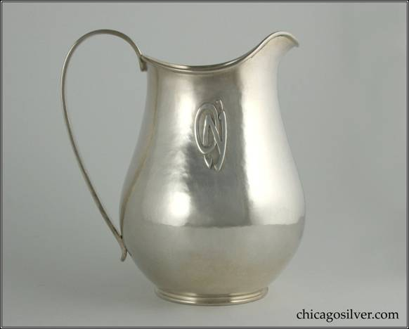 "Kalo pitcher, with wide bottom tapering to thin neck and then flaring out slightly, with arching spout, looping heavy strap handle, applied O'N monogram on side.  On small ring foot, with applied wire to rim.  Lovely hammering and shape.  7"" H and 6-1/4"" W.  STERLING / HAND WROUGHT / AT / THE KALO SHOPS / CHICAGO / AND / NEW YORK / 9440"