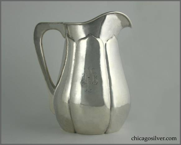 "Kalo pitcher, water, with wide melon ribs each coming to a point beneath the rim, flat bottom, flat edge harp-shaped hollow handle, applied wire on rim, engraved ""IFB"" mono on side.  9"" H and 7-1/2"" W.  STERLING / HAND WROUGHT / AT / THE KALO SHOPS / CHICAGO / AND / NEW YORK / 7533"