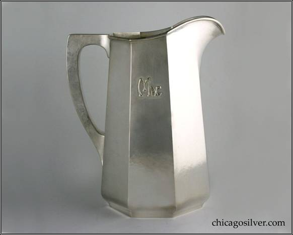 "Kalo pitcher, water, tall tapered paneled form on low self-foot with applied ""Mac"" mono, arching spout, heavy wire applied to rim, and harp-shaped square-section hollow handle with flat top.  Nicely hammered surfaces.  Heavy.  From the estate of Allison & Elizabeth Macdonald of E. Topsham, VT.  10"" H and 8-1/4"" W.  STERLING / HAND WROUGHT / AT / THE KALO SHOP / G574LL"