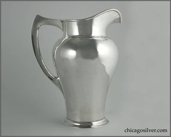 "Kalo pitcher, tall, on spreading foot, with narrow bottom flaring to bulbous shoulder, tall cylindrical neck with high arching spout, flat angular hollow harp-shaped handle that comes to a point in the corner.  Applied wire to rim and nicely hammered surfaces.  10"" H and 7-7/8"" W.  STERLING / HAND WROUGHT / AT / THE KALO SHOP / E508 / 5 PINTS"