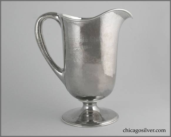 "Kalo pitcher, trophy, with cylindrical body necking in at bottom to wide round foot, and flaring out at top to arching spout.  Looping hollow handle, applied wire to rim.  Nicely hammered surfaces.  Engraved on side is ""Onwentsia Club / Won by / Wayne Chatfield-Taylor"".  Engraved on top of foot is ""Choice Score Cup"".  Engraved on underside of foot is ""Presented by / W. A. Alexander / and / Thomas Taylor Jr."" 8"" H and 7-1/8"" W.  STERLING / HAND BEATEN / AT / KALO SHOPS / PARK RIDGE / ILLS. / 9283"