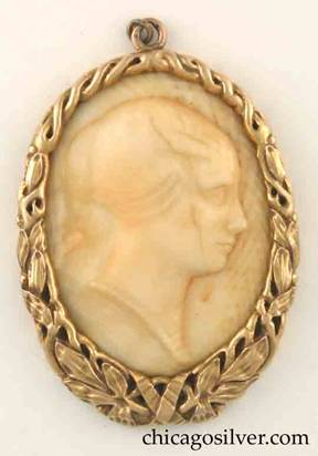 Potter Studio pendant, gold, oval wreathlike frame of leaves and ribbons, thicker at the bottom, centering ivory cameo of woman facing right, with hair pulled back.  With loop at top for chain.  Heavy.