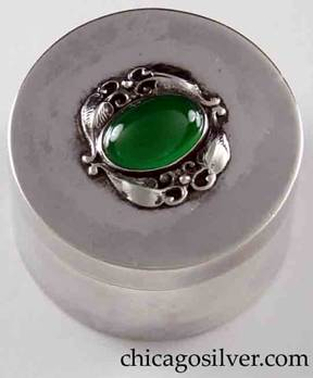 Potter Studio stamp box, cylindrical, with slot in side for stamps, removable cover centering oval green bezel-set chrysoprase stone surrounded with applied leaves and vines.