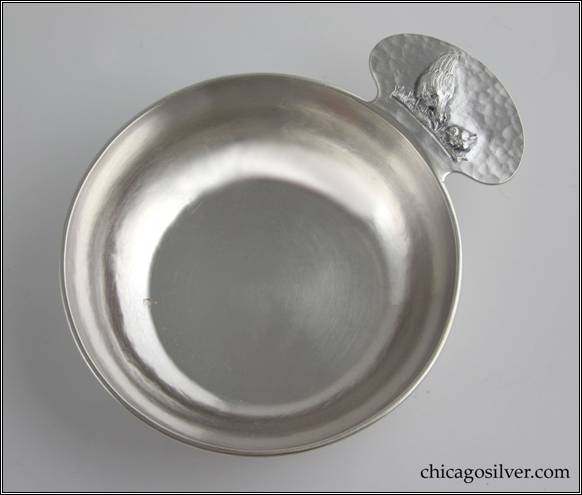 Kalo porringer, round, flat bottom form with rounded tab handle and applied wire rim.  Handle has chased and repoussé decoration of hen standing on grass beside small chick.