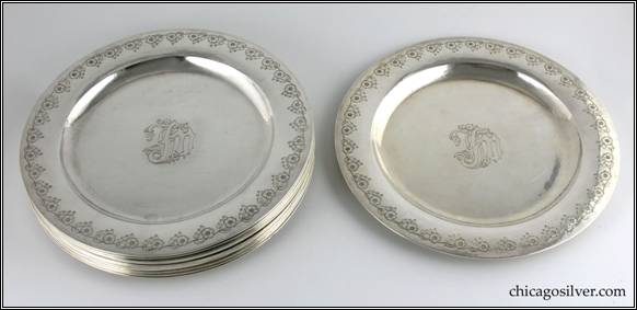 "Kalo plates, dinner, set of twelve (12), with deeply chased flowers around outside and a ""JFM"" monogram in center on front"