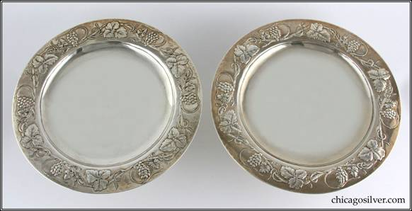 Kalo compotes, low, matching pair (2), broad, round pedestal base supporting shallow dish with raised flange which has a fine chased and repousse grapevine and leaf design