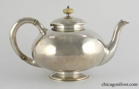 "Kalo tea pot, raised globe form on low pedestal foot, arching spout and looping hollow handle, broad overlapping domed lid with turned ivory finial, ivory insulators on handle, hammered surface.  Engraved D monogram on side.  6-1/2"" H and 10-1/2"" W.  marked:  STERLING / HAND WROUGHT / AT / THE KALO SHOP"