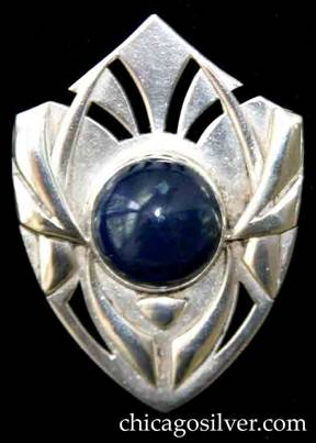 Art Silver Shop brooch / pin, shield-shaped, with sides that curve down gently to a point on the bottom, and upward with a slightly concave curve to a point at the top.  Applied tusk-shaped forms over curving saw-pierced details, centering an oval bezel-set blue cabochon lapis or sodalite stone.
