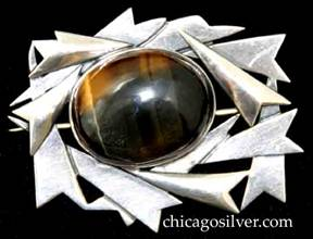 Art Silver Shop brooch / pin, made of overlapping cutout and applied arrowhead forms on a complex cutout frame centering a large oval bezel-set cabochon tigers-eye stone.