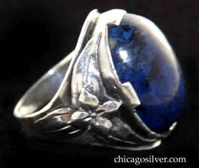 Art Metal Studios ring, with large dark blue oval lapis or sodalite bezel-set cabochon stone with four additional wide prongs, with an applied and chased flower over three long chased leaves on each side.
