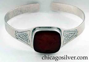 Art Metal Studios bracelet, with large intaglio carnelian stone, open back and tapering rounded ends.  Stone is bezel-set with profile of helmeted Greek or Roman soldier.  Chased design on both sides of stone.  Hammered surface.