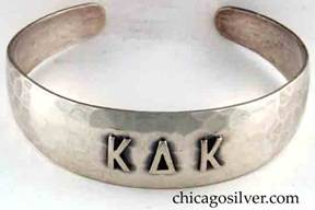 "Art Metal Studios bracelet, with open back and tapering rounded ends, applied ""K Δ K"" mono, nice hammering."