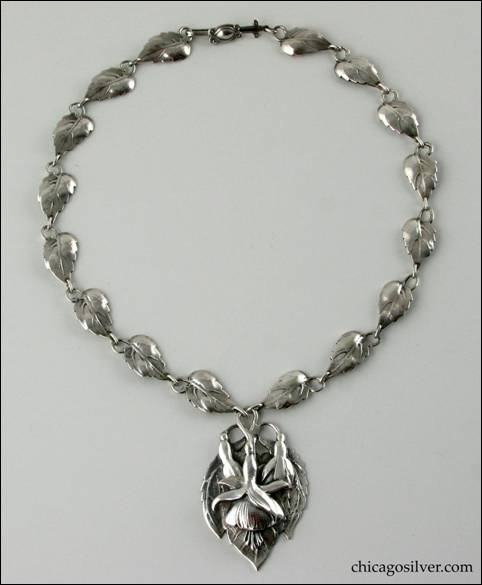 Necklace, silver, composed of 16 leaf-form links each with a stem that curves around and forms a loop, centering a large pointed oval plaque with chased fuchsia blossoms and leaves.  Plaque is heavy and dimensional.  Long thin interesting clasp with applied curving decoration.