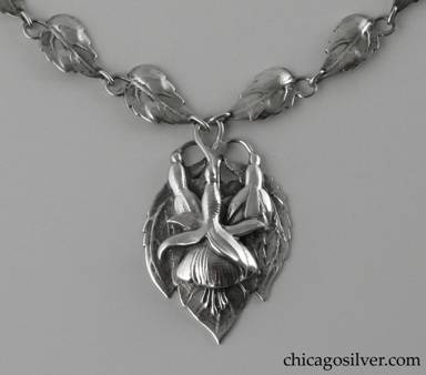 Peer Smed necklace, silver, composed of 16 leaf-form links each with a stem that curves around and forms a loop, centering a large pointed oval plaque with chased fuchsia blossoms and leaves.  Plaque is heavy and dimensional.  Long thin interesting clasp with applied curving decoration.